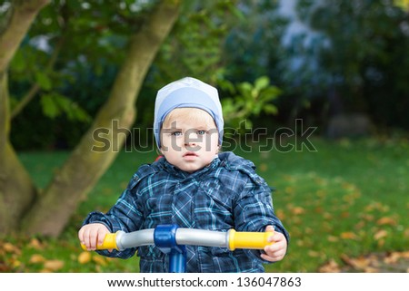 Little toddler boy in autumn park on bicycle - stock photo