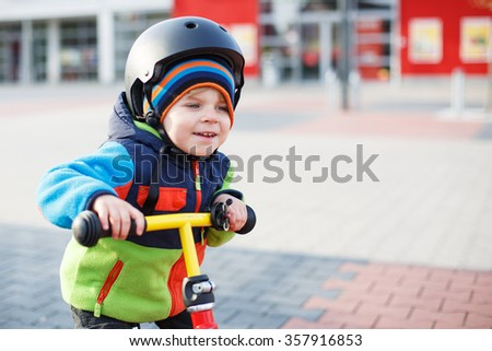 Little toddler boy learning to ride on his first bike  in the city. Cute kid boy in safety helmet having fun outdoors in spring. - stock photo