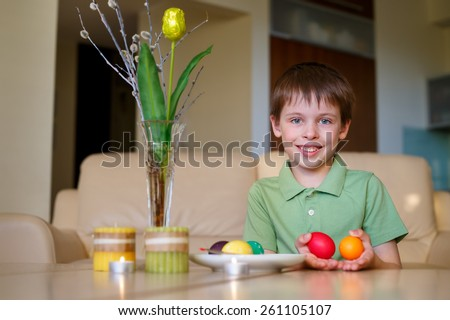 Little toddler boy painting colorful Easter egg for hunt - stock photo