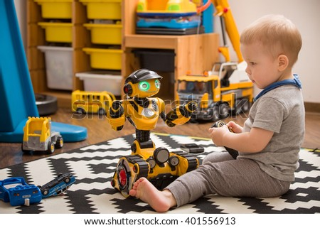 Little toddler boy playing with funny robot toy at home, indoors. Innovation technology concept. Children and technology. - stock photo