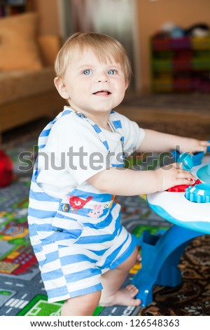Little toddler boy playing with  toys indoor - stock photo