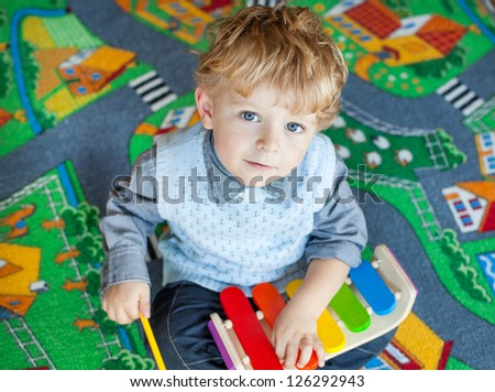 Little toddler boy playing with wooden music toy indoor - stock photo