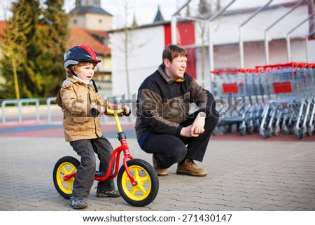 Little toddler boy with bicycle and his father in the city. - stock photo