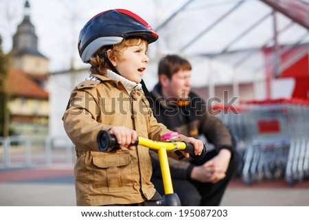 Little toddler boy with bicycle and his father in the city. Happy family of two - stock photo
