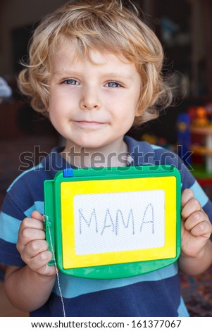 Little toddler boy with painting board writes his first word mama - stock photo