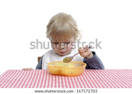 Little toddler eating by herself - stock photo