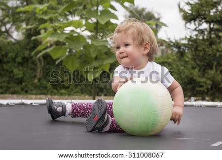 Little toddler first time on trampoline - stock photo