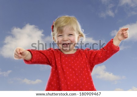 Little toddler girl in red outdoors against a blue sky with clouds - stock photo