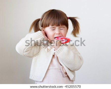 Little toddler girl is biting a large piece of hard candy - stock photo