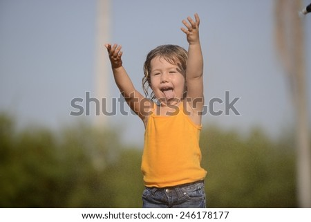 little toddler girl playing and dancing in the summer rain - stock photo