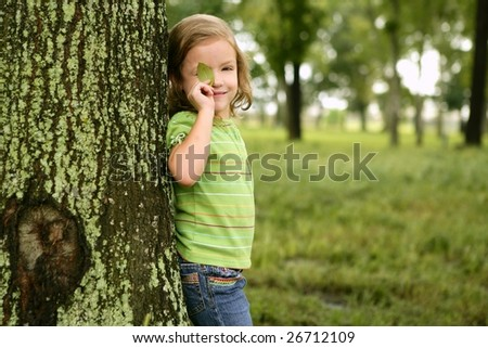 Little toddler girl playing on the park with a green leaf - stock photo