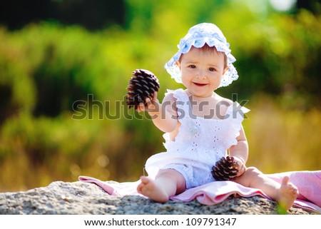 Little toddler girl sitting in green summer park - stock photo