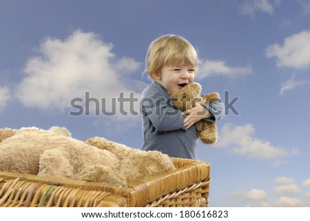 Little toddler girl with teddy bears outdoors against a blue sky with clouds - stock photo