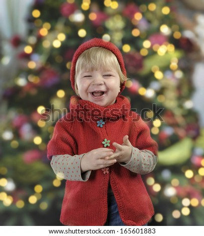 little toddler in front of a christmas tree - stock photo