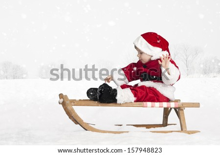 little toddler in santa claus outfit on a sledge outdoors in the snow - stock photo