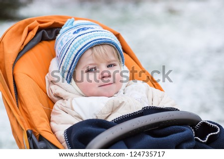Little  toddler one year old in warm winter clothes and orange pram outdoor - stock photo