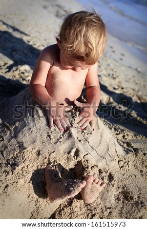 Little toddler overwhelmed in beach sand - stock photo