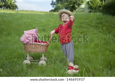 Little toddler playing with a pram outdoors in the garden - stock photo