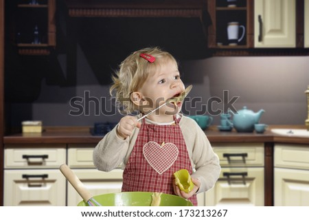 little toddler tasting pastry in the kitchen - stock photo