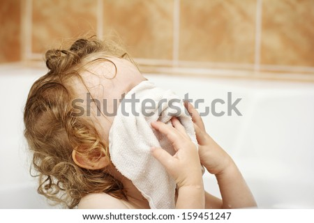 Little toddler washing face in the bathroom - stock photo