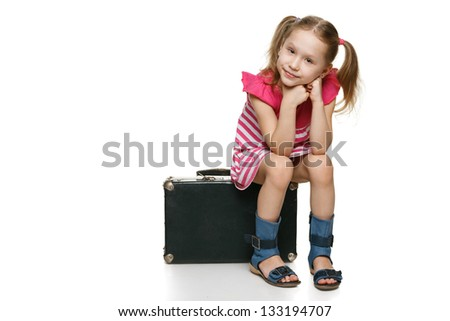 Little tourist. Little girl with sitting on the old fashioned suitcase in full length, over white background - stock photo
