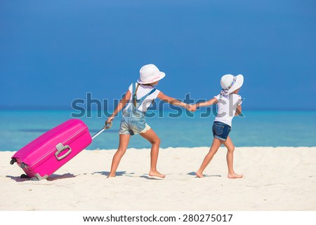 Little tourists girls with big suitcase on tropical white beach  - stock photo