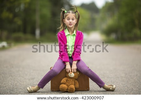 Little traveller girl on the road with a suitcase and a Teddy bear. - stock photo