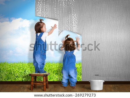 Little twins doing repair at home, hanging wallpaper. Renovation concept. - stock photo