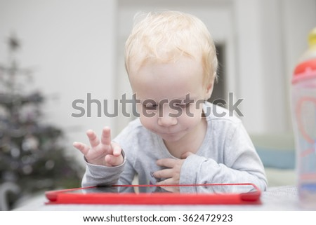 Little two years girl uses a tablet on a sofa - stock photo