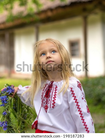 Little ukrainian girl watching magpie and holding her circlet of flowers - stock photo