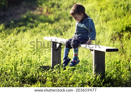 little upset boy sitting on a bench in a field - stock photo