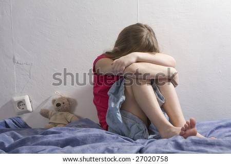 little upset girl sitting on the bed hugging her knees - stock photo