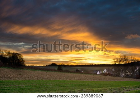 Little village next to some fields at sundown in the fall - stock photo