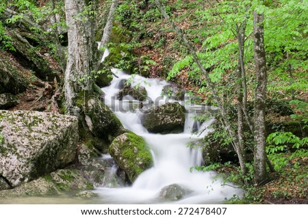Little waterfalls in a peaceful wood. Green background and the dark rocks contrast. Soft trasparences of the water and waterfall motion blur. - stock photo