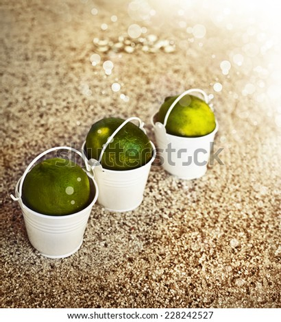 Little white buckets with limes on the sandy beach. Summer holiday concept background, travel themes with cocktail umbrella, handmade paper as a copy space - stock photo