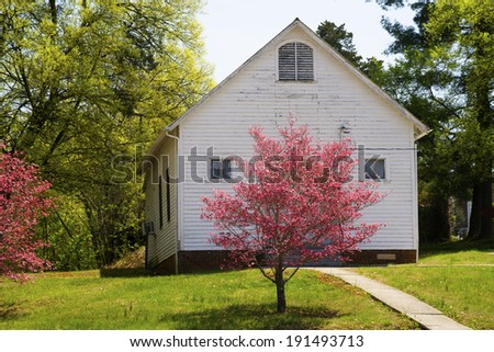 Little white church in Appalachia with pink Dogwood Trees. - stock photo