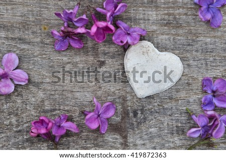 little white heart on wooden plank  with petals of lilac - stock photo