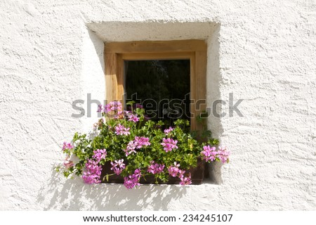 Little window with flowers at a typical village building in South Tyrol, Italy. - stock photo