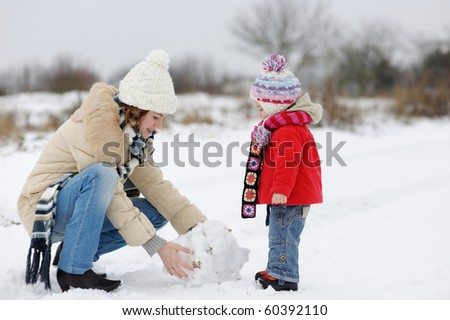 Little winter baby girl and her mother - stock photo