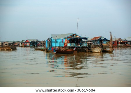 little wooden barges floating down the Mekong - stock photo