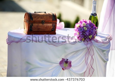 Little wooden trunk stands on a table behind a bottle of champagne - stock photo