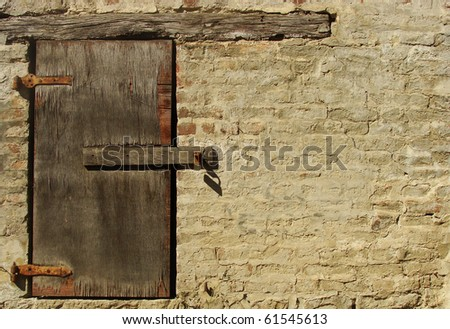 little wooden window with padlock in beige painted brick wall - stock photo