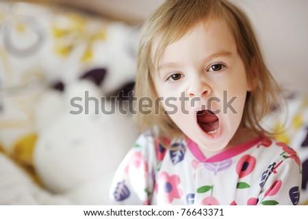 Little yawning toddler girl in pajamas on sunny morning - stock photo
