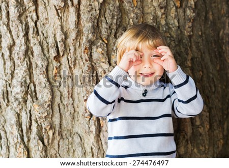 Little 4 year old blond caucasian boy in front of an old and massive tree pretending to take a picture with his hands. - stock photo