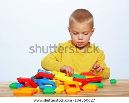 little 3 year old toddler boy playing with bright plastic pyramid blocks over light studio background. - stock photo
