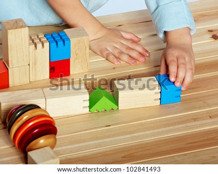 little 3 year old toddler boy playing with bright wooden blocks on a wooden table - stock photo