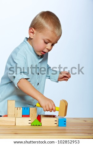 little 3 year old toddler boy playing with bright wooden blocks on a wooden table over light blue studio background - stock photo