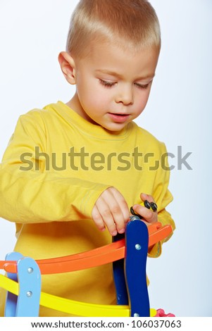 little 3 year old toddler boy playing with wooden cars on studio background - stock photo
