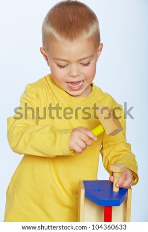little 3 year old toddler boy with a toy wooden hammer and toolbox over studio background - stock photo