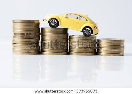 Little yellow car over a lot of stacked coins - stock photo